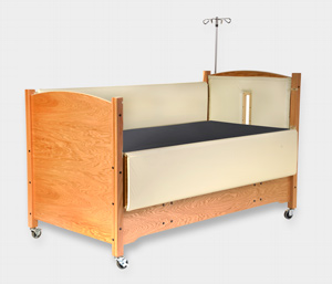 SleepSafe II Hi-Lo Bed in Oak with Pads and IV Pole with an opening for IV tubing.